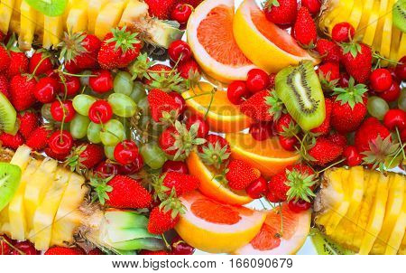 Fruit sliced oranges banana kiwi cherries grapefruit strawberries grapes and pineapple lying on a white plate close-up.