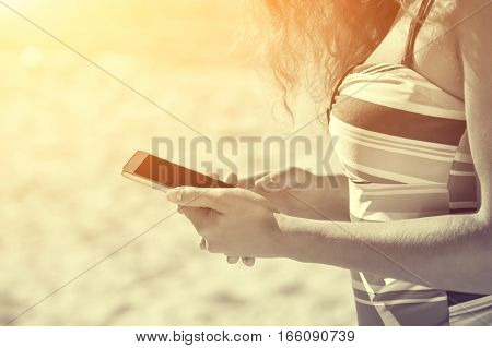 Young attractive smiling young woman on the beach holding a mobile phone.