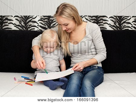 Young mother is drawing with her daughter on the sofa
