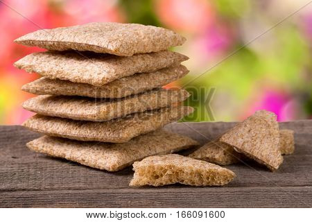stacked crisp bread on a wooden table with blurred garden background.