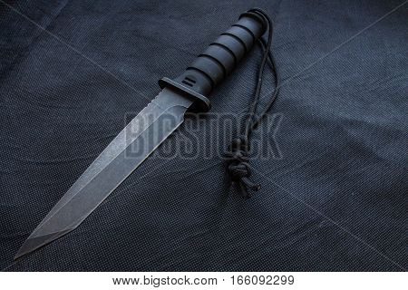 Knife for the military. Black background. Black iron