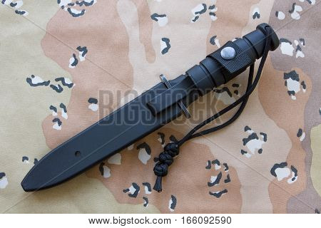 Tactical knife in a case on the sand camouflage. Knife for the military.