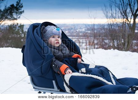 Little boy sitting in a sleigh. Cute little boy sitting on her sledge in winter day. Winter play snow sledding - beautiful boy has a fun on snow. Little boy enjoy a sleigh ride.Outdoor fun for family Christmas vacation.