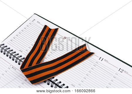 In an open diary sheet is St. George's ribbon in the form of the letter V