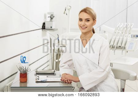 Smiling cheerful dentist wearing in a white coat. She sitting at table. Medical instruments and tablet are on table