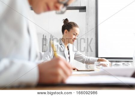 Signing documents in the office. Office work. Women unsubscribed documents