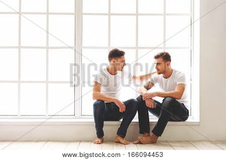 Joyful two male gays are sitting near window and talking. Man is embracing his friend and smiling