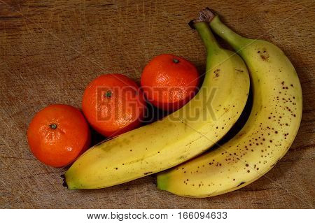 Tangerines and bananas - raw fruits - fresh fruit