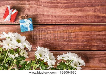 White chrysanthemum flowers with gift boxes on wooden table. Holiday card.