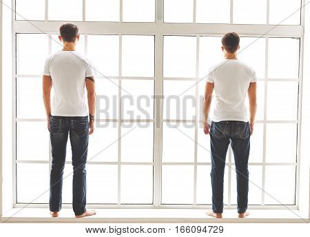 Two confident men are standing on windowsill and looking forward. Focus on their back