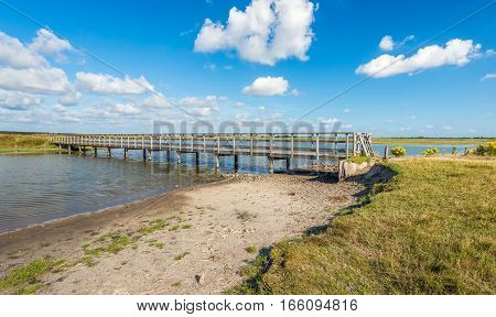 Natural creek area with a small sandy beach and a wooden footbridge over the water. It's a sunny day in the summer season with a blue sky and beautiful white clouds.