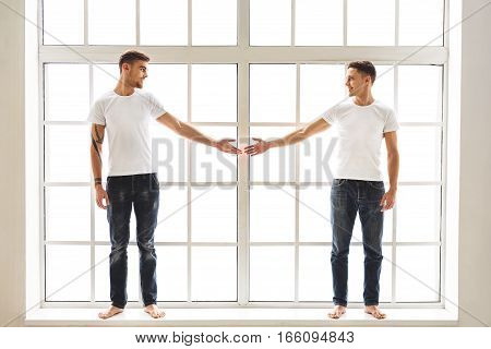 I love you. Joyful male gays are looking at each other and smiling. They are standing near window and stretching arms to join them