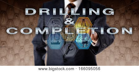 Business administrator in blue suit pushing DRILLING & COMPLETION on a virtual interactive computer screen. Oil and gas industry technology concept for getting a petroleum well ready for production.
