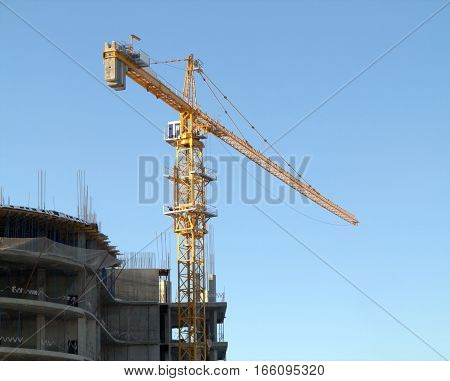 Yellow hoisting tower crane in construction process on top of construction modern building over blue cloudless sky