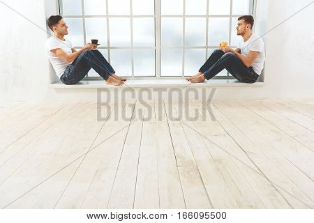 Friendly talk. Cheerful two men are drinking tea while speaking. They are sitting on windowsill and smiling