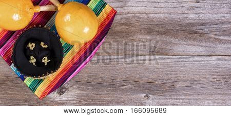 Flat view of maracas sombrero and sombrero on rustic wooden boards for Cinco de Mayo concept.