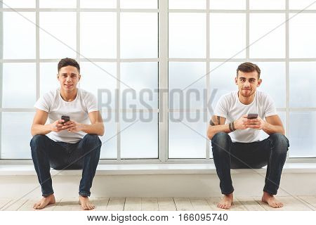 Happy young guys are holding mobile phones and smiling. They are sitting near window and looking at camera with joy