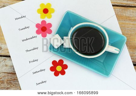 Weekdays listed on white paper, cup of coffee and colorful flowers