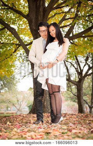 Couple maternity photo in fall under the tree with leaves on the ground