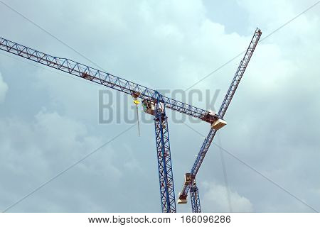 High blue construction hoisting tower cranes over cloudy sky