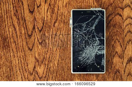 Top view of Smartphone with broken screen on wooden table.