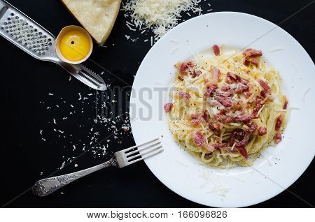 Pasta Carbonara. Spaghetti with bacon and parmesan cheese. Pasta Carbonara on white plate with parmesan on dark background. Italian food concept. Top view.