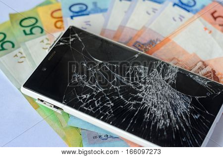 Broken smartphone lying on money banknotes on a White background. Losing money concept