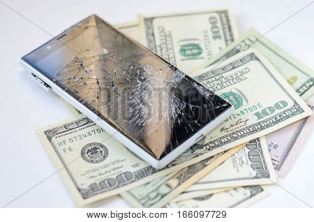 Smartphone with broken display lying on money banknotes on white background. Need new smartphone concept