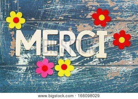 Merci (thank you in French) written with wooden letters on rustic surface and colorful flowers