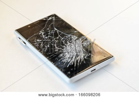 Smartphone with broken display on white background