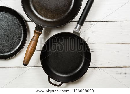 Several empty cast-iron frying pans on a white wooden background. View from above. Space for text.
