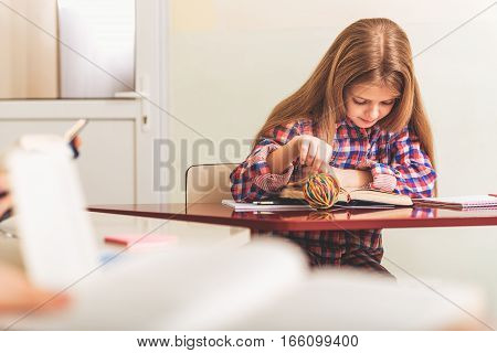 Interested girl is sitting in light room. She looking through information at open printed volume
