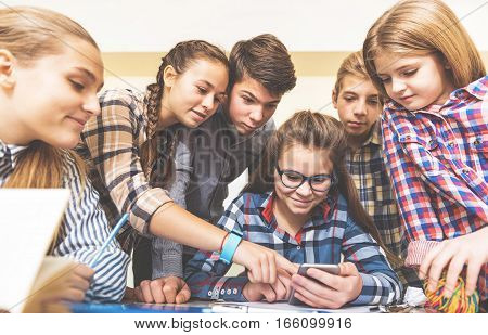 Smiling girl is sitting in room among her friends. They are looking at tablet