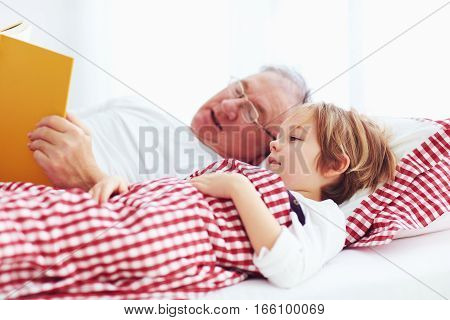 grandpa reading a book to his ill grandchild in bed