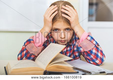 Exhausted girl is sitting near desk full of equipment for study. She touching her head and looking at camera with sadness