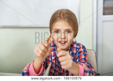 Surprised smiling girl is sitting and looking at camera with enthusiasm and admiration