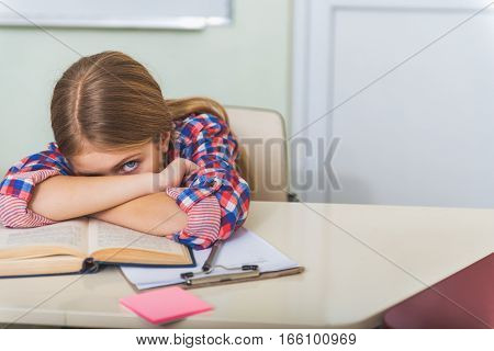 Serious exhausted girl is sitting near table and putting head on crossed hands. She looking at camera with one eye