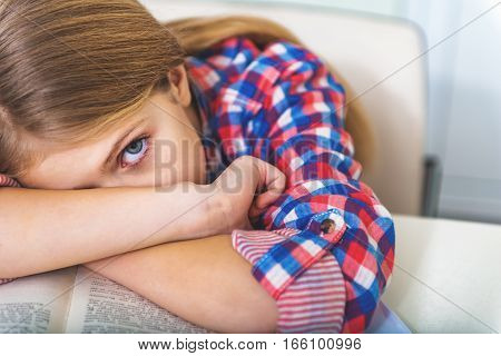 Angry tired female teenager is sitting near desk and placing head on crossed hand. She looking at camera with one eye