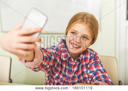 Hilarious female teenager is sitting at desk. She making photo of herself