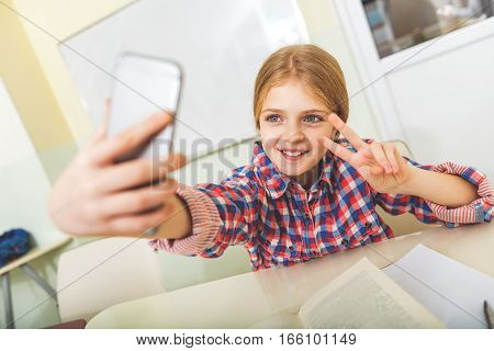 Happy girl is sitting near polished desk. She looking at mobile and making funny photo