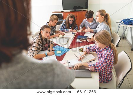 Serious attentive pupils are sitting in classroom. They studying and looking at teacher