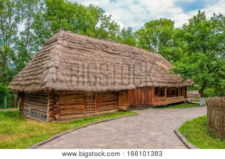 Ancient traditional ukrainian rural cottage with a straw roof in cloudy summer day