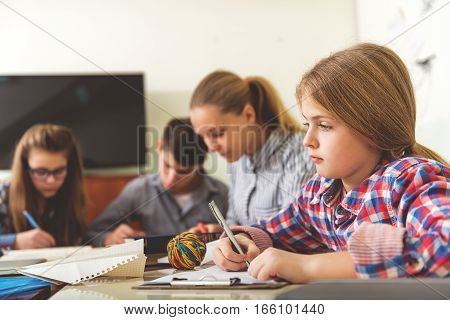 Intent pupils are sitting near working table. Focus on thoughtful girl with pen in her hand