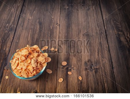 Tasty corn flakes in bowl. Rustic wooden background. Healthy crispy breakfast snack. Place for text. Top view, flat lay. Text space.