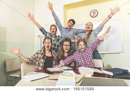 Happy smiling pupils are in classroom. They playing at break between lessons and raising their hands up