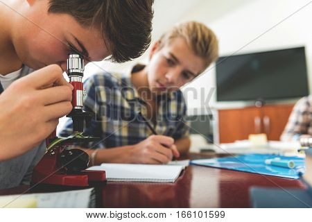 Attentive boys are sitting near desk. Teenager using microscope and partner is noting results