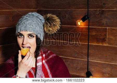 Young beautiful dark-haired woman smiling in winter clothes and cap with tangerines on wooden background