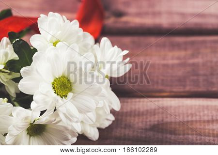 White chrysanthemum flowers with red ribbon on wood.