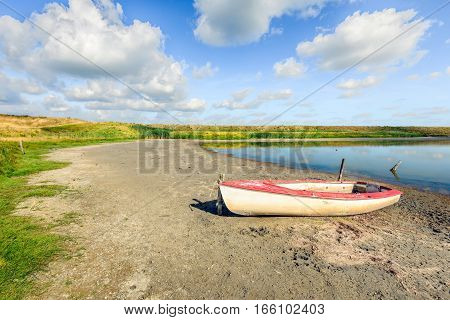 Natural landscape with in the background an embankment with yellow blooming wild flowers and in the foreground a red and white boat on the shore near the water.