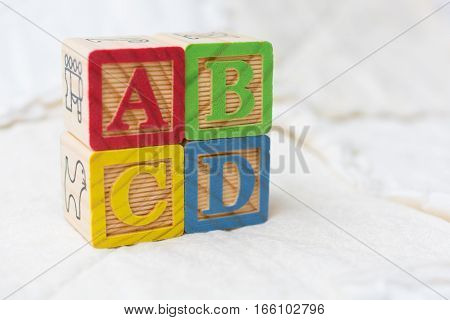 Wooden Alphabet Blocks On Quilt Spelling Abcd Stacked On Angle